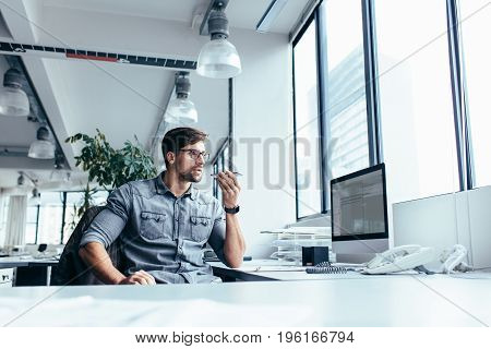 Serious young businessman sitting and talking on mobile phone in office. Creative professional sitting at his workplace.