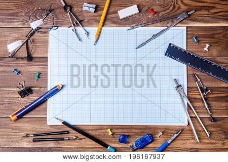 Graph paper with copyspace and student material on wooden table. Top view