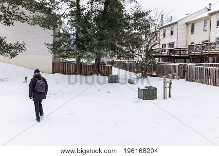 Man Walking In Neighborhood On Snow Covered Ground