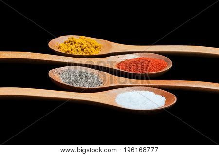 Spices in wooden spoons. Isolated on black background. Selective focus. Food concept.