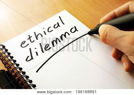 Ethical dilemma written in a note on a table.