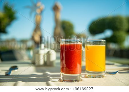 Full Glasses Of Orange Juice And Tomato Juice On Table Side By Side With Sun Light