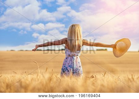 Happy young woman blonde in a wheat field with a straw hat in hand