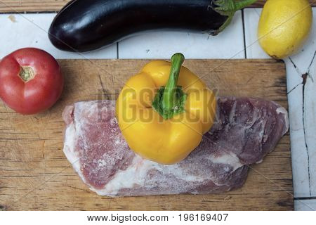 Frozen piece of meat on a wooden cutting board and yellow bell pepper, red tomato and eggplant on the table. Close up image