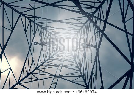 High voltage tower and gray cloud on sky with sunlight.