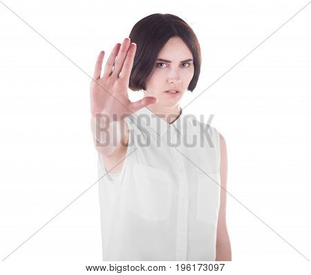 A serious young woman making stop gesture with her hand, isolated on a white background. A strict girl with short hair and in fashionable white blouse making stop sign. Protest concept.