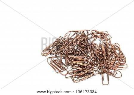 Bunch of old office copper paperclip. Partially isolate on a white background.