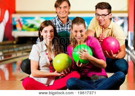 Group of four friends in a bowling alley having fun, holding their bowling balls