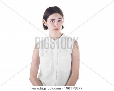 Shocked and surprised young lady looking at the camera, isolated on a white background. An attractive girl is annoyed, shocked or bewildered. Sad woman.