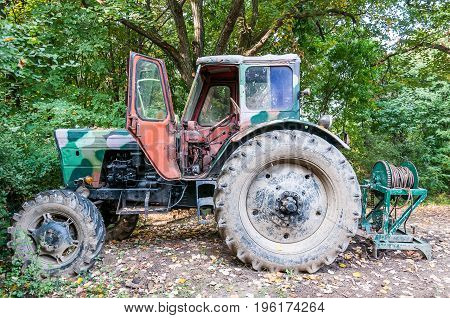 Old abandoned rusty and camouflage vintage tractor in the forest.