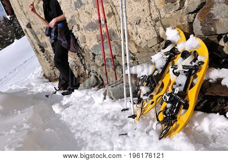 snowshoes and sticks against a wall with hiker