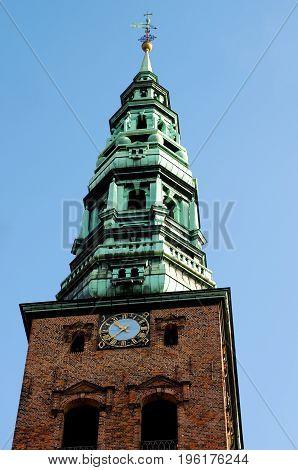 Spire of St. Nicholas Church against Blue Sky Outdoors Bottom View. Copenhagen Denmark