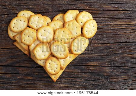Crackers biscuits with cheese flavor in shape of heart on dark wooden table top view