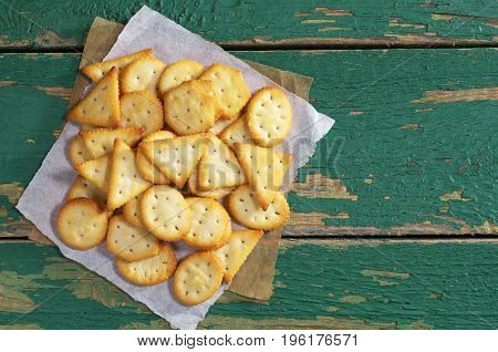 Crackers biscuits with cheese flavor on old green wooden table. Top view with copy space