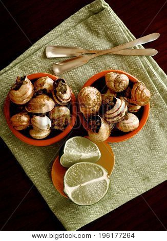 Two Bowls of Delicious Escargot with Garlic Butter Silver Forks and Sliced Lime closeup on Green Napkin. Top View