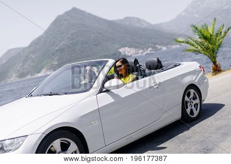 Young Women In White Cabriolet Car Driving Everywhere And Looking For Freedom And Fun