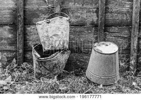 Old buckets stained in cement on a wooden background black and white photo