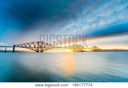 Long exposure of the Forth Rail bridge over the Firth of Forth in Scotland. With blue sky and water taken during the golden hour