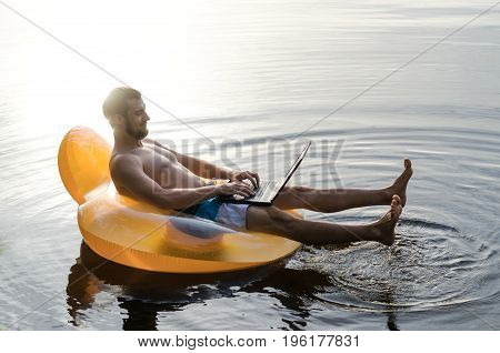 Businessman Working On A Laptop On An Inflatable Ring In The Water, Copy Space.