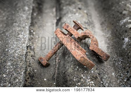 Old rusty metal clamp on an asbestos sheet selective focus shallow depth of field