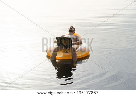 A Man With A Laptop On An Inflatable Ring In The Water At Sunset, Free Space.