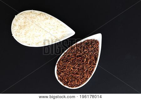2 kind of raw Thai rice Thai Jasmine rice(Hom Mali ) and Brown Rice (Khao Dum) in white cups on black background with copy space