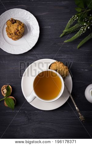 Herbal tea and homemade oatmeal nut cookies on a wooden background. Top view