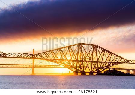 Close up long exposure of the Forth Rail bridge over the Firth of Forth in Scotland. taken at sunset with golden sky