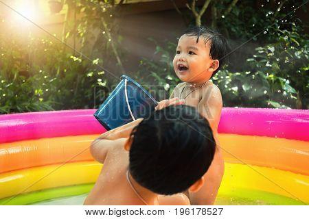 Children play water bucket together in colorful kiddie pool with nature background.