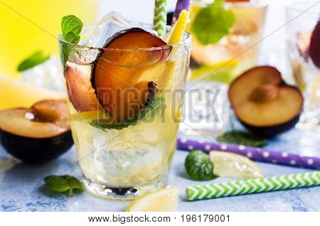 Drink with plums and lemon in the glass. Selective focus.