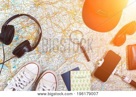 Accessories for travel. Passport, cap, smart phone and travel map. Top view. Holidays and tourism concept. Copy space. Still life. Flat lay. Sun flare