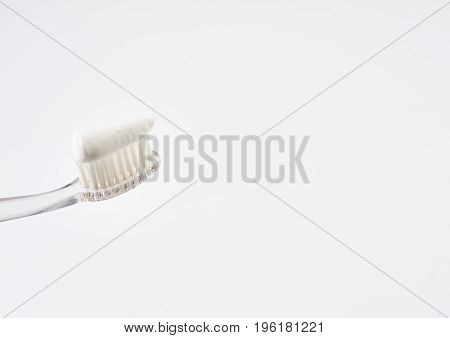 Clear new toothbrush with white mint toothpaste isolated on white background with copy space. Dental hygiene and care.