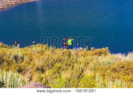 Family Fishing On Shoreline Of Local Lake