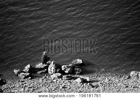 old fisherman sit on river. poorness and rural life concept