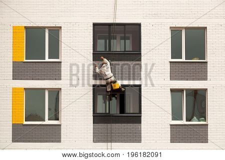 industrial climbers climb on a facade of the modern building