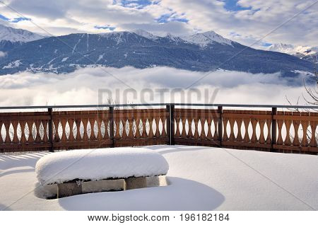 snowy terrace with bench and railing above clouds