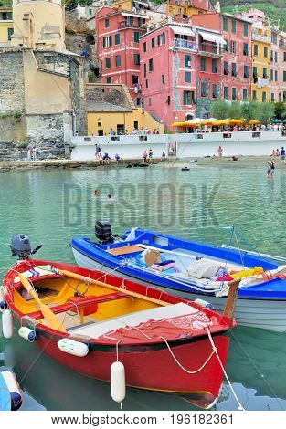 colorful boats on water in front of a scenic Italian village