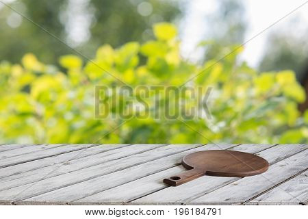 Natural bokeh abstract pattern background with tabletop and display for your product. Kitchen outdoors with tabletop and cutting board.