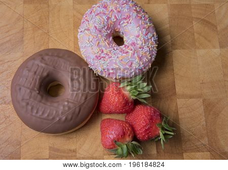 Strawberry and chocolate donuts on a wooden background with strawberries
