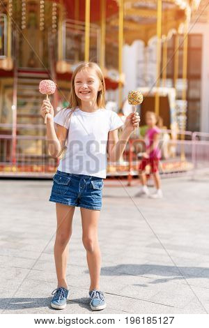 Cute little girl eating candy apple and posing at fair in amusement park