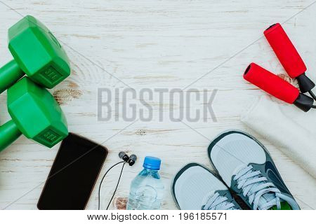 Fitness, healthy and active lifestyles Concept, Jump rope, dumbbells, sport shoes, bottle of water, smartphone with headphone on white background. Top view
