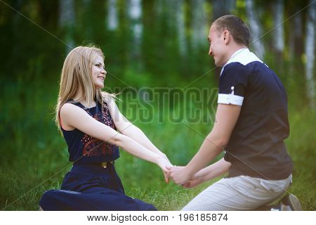 Lovers have fun dating in forest. Cute healthy young girlfriend and handsome boyfriend sitting on gtass. happy family relationship concept