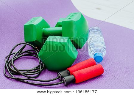 Fitness, healthy and active lifestyles Concept, Jump rope, dumbbells, bottle of water on karemat
