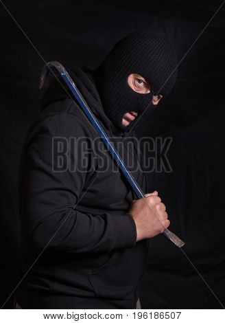 Vertical image of , unrecognisable threatening man with a balaclava mask and holding a crowbar