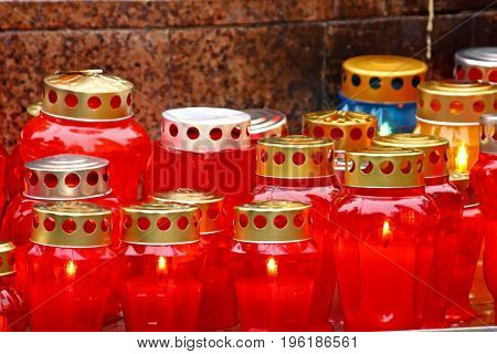A lot of illuminated votive candles glows on a grave lantern