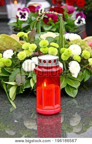 Illuminated votive candle glows on a grave lantern