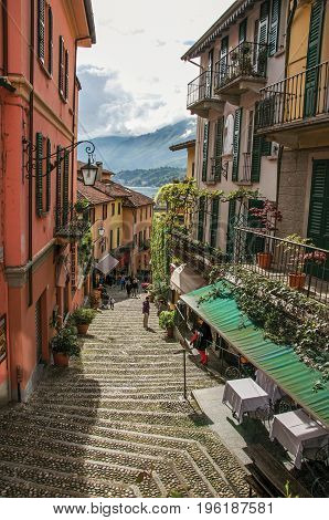 Como, Italy - May 06, 2013. View of alley in hillside, buildings with bindweed and Lake Como in Bellagio, a charming village between the lake and the mountains of Alps. Lombardy region, northern Italy