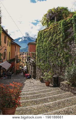 View of alley in hillside, buildings and wall with bindweed in Bellagio, a charming tourist village between the lake and the mountains of the Alps. Located in the Lombardy region, northern Italy
