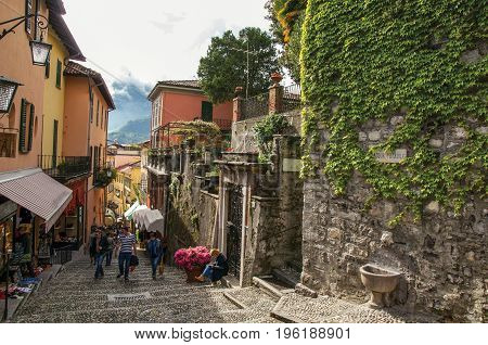Como, Italy - May 06, 2013. View of alley in hillside, buildings and wall with bindweed in Bellagio, a charming village between the lake and the mountains of Alps. Lombardy region, northern Italy