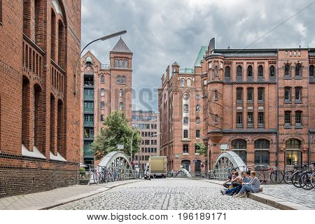 Hamburg , Germany - July 14, 2017: Young folks sitting in the streets of the famous Speicherstadt of Hamburg, EUrope